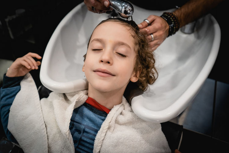 High angle view of boy getting hair wash at hair salon