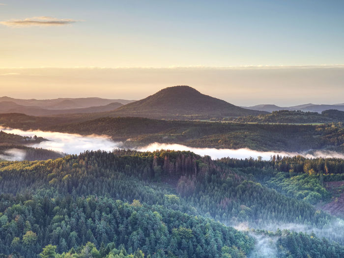 Sunset hills over clouds landscape in bohemia. beginning of autumn