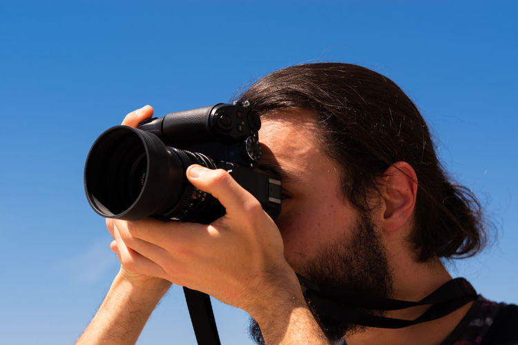 Portrait of man photographing against sky