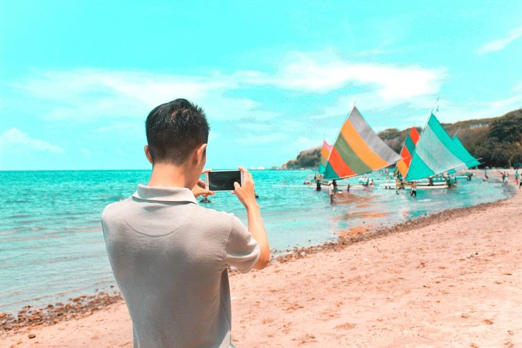 Rear view of man photographing nautical vessels at beach