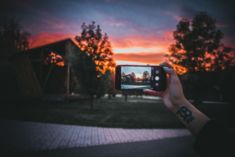 Man photographing through smart phone at sunset