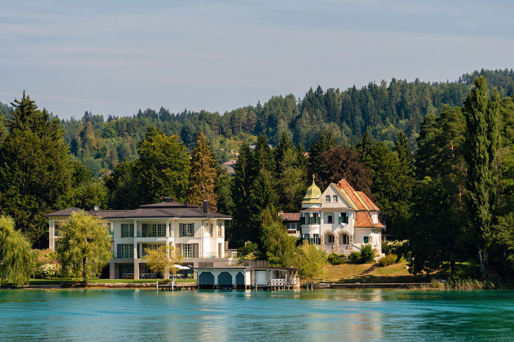 WORTHERSEE, AUSTRIA - AUGUST 08, 2018: Great scenery from the boat to the shore line of the lake, beautiful buildings, mountains, forests, highways. Tourists who enjoy a variety of water recreation types. Nature Day Outdoors Austria Carinthia Carinthian Lakes Tourist Tourists Lake Wörthersee Recreation  Leisure Landscape Water Sea Boats Motorboat Speedboats Summer People Holidays Fun Travel Beach Resort Lifestyle Sunny Rest Joy Waves Europe Alps Alpine Alpine Lake Architecture Tree Built Structure Building Exterior Building Plant House Residential District Waterfront No People Beauty In Nature Sky Mountain Scenics - Nature Tranquility Tranquil Scene Luxury Swimming Pool