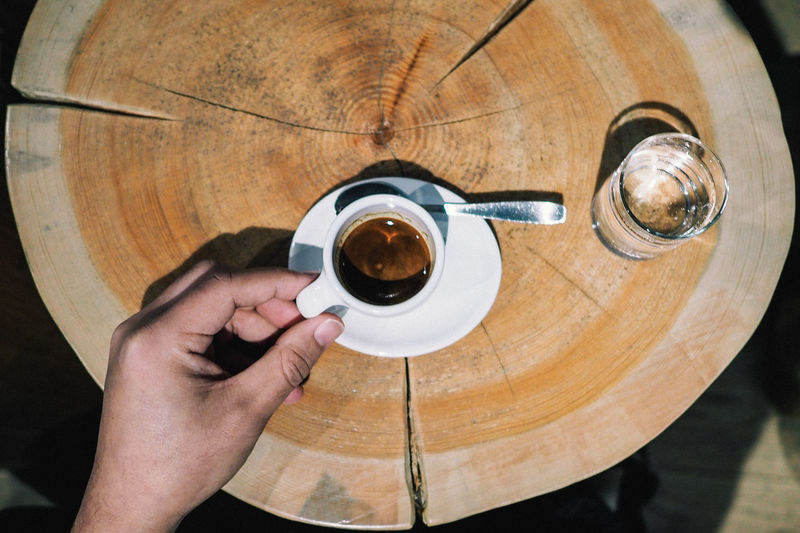 Cropped Image Of Hand Holding Cup of Espresso At Wooden Table Adult Caffeine Close-up Coffee - Drink Coffee Cup Colour Image Directly Above Drink Drinking Espresso Food And Drink Freshness High Angle View Holding Human Body Part Human Hand Indoors  Low Section One Man Only One Person Real People Refreshment Table Table Setting Wood - Material