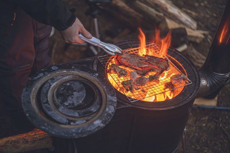 Midsection of man preparing food on camp barbecue grill
