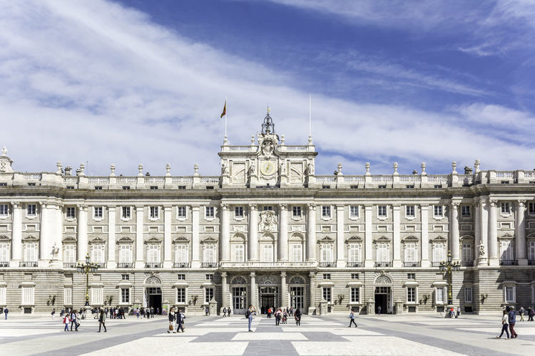 Tourists visiting royal palace of madrid against sky