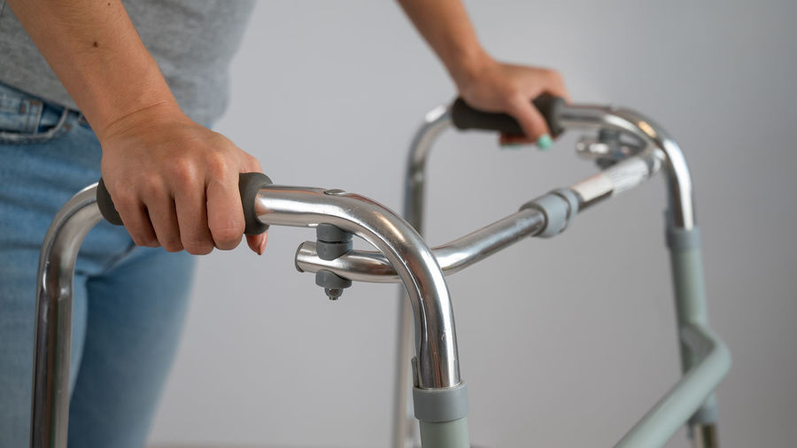 Close-up of hand holding faucet against blurred background