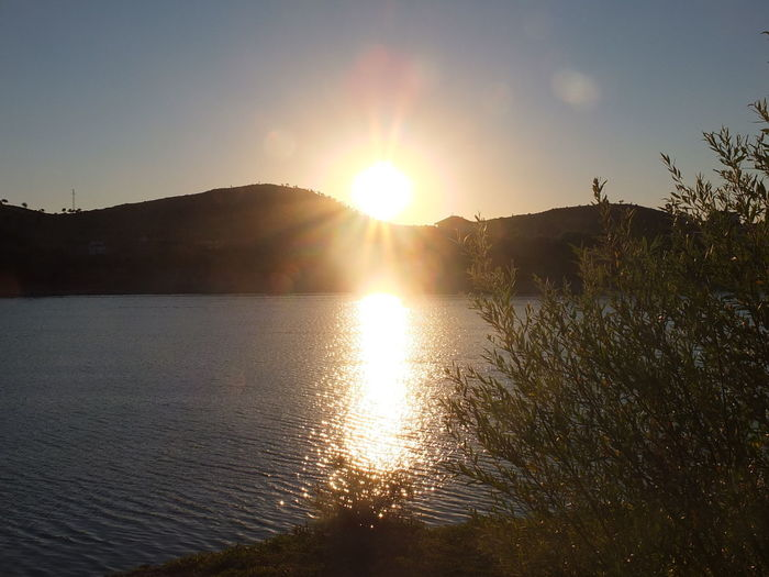 Sky Sunlight Sunset Water Beauty In Nature Sun Scenics - Nature Tranquil Scene Tranquility Lens Flare Nature Mountain Sunbeam No People Reflection Lake Plant Tree Idyllic Outdoors Bright