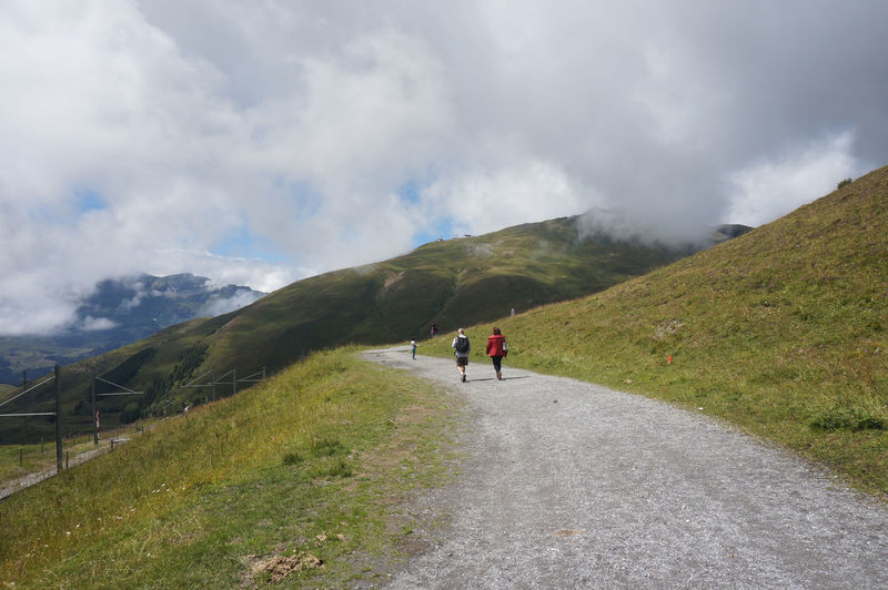 People walking on road by mountain against sky