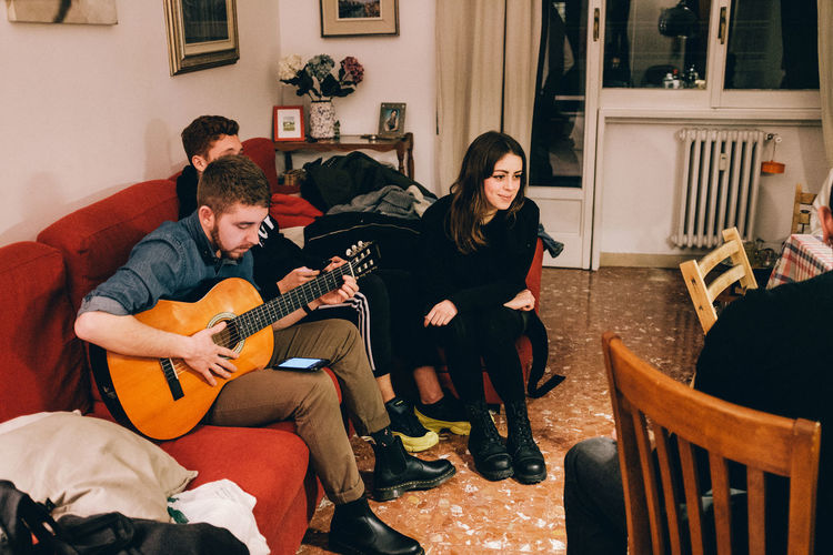People playing guitar on sofa at home