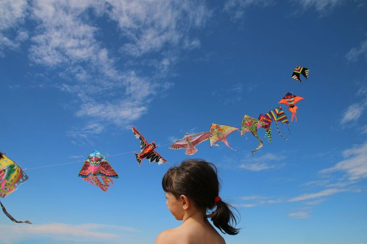 Low angle view of girl by kites flying in sky