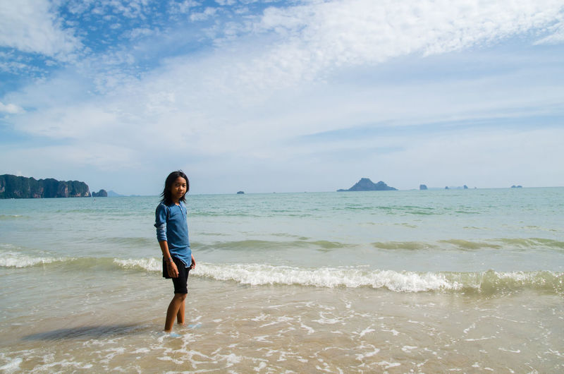 Portrait Of Teenage Girl Standing Against Sea At Beach
