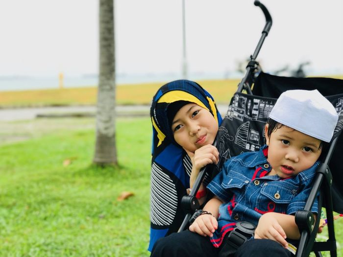 Portrait Of Sister With Brother Sitting On Baby Carriage At Park