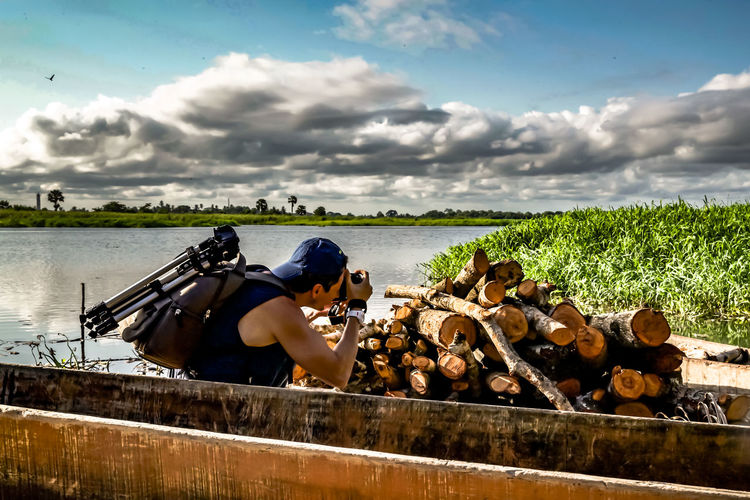 Side view of man photographing stack of logs