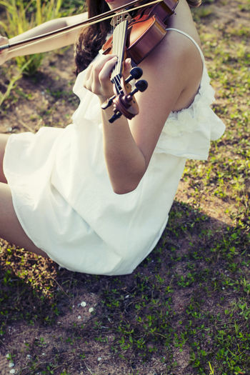 Midsection Of Woman Playing Violin On Field