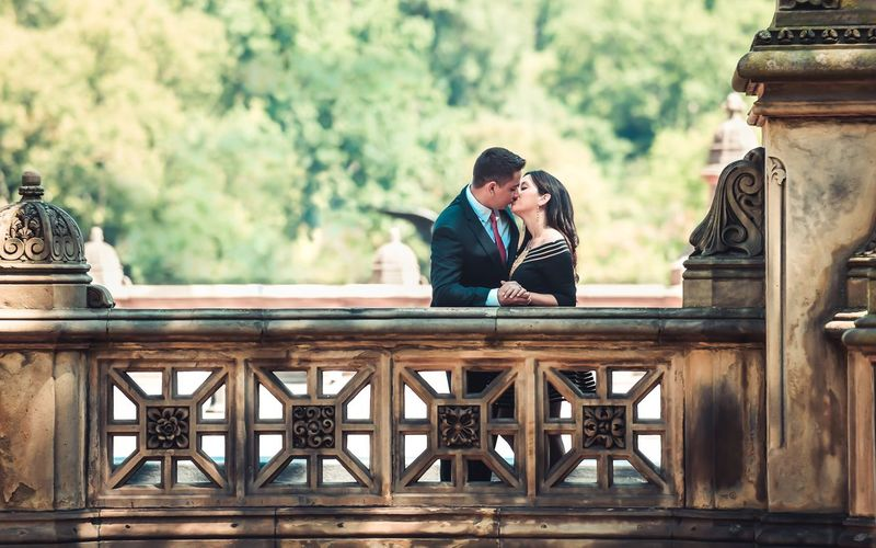 Couple Kissing By Railing On Footbridge