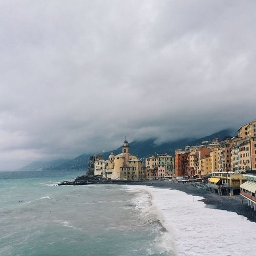 Residential buildings by sea against cloudy sky