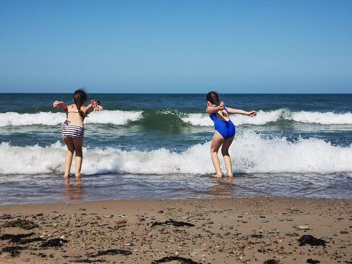 Full length of girls at beach against clear sky