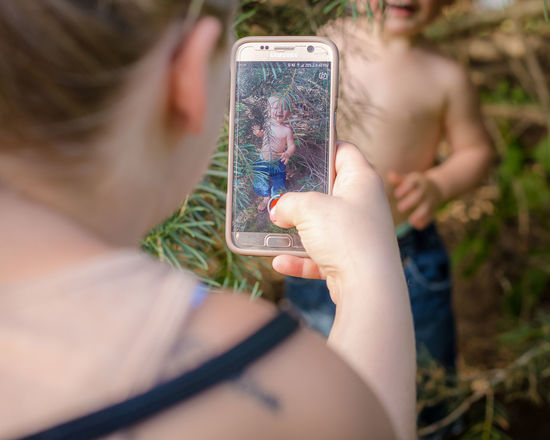 Family Activity Childhood Communication Connection Day Hand Leisure Activity Lifestyles Mobile Phone Nature One Person Outdoors Photography Themes Plant Portable Information Device Real People Selective Focus Smart Phone Technology Wireless Technology Women This Is Family Visual Creativity
