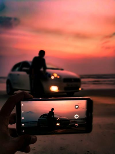 Silhouette man photographing car against sea during sunset