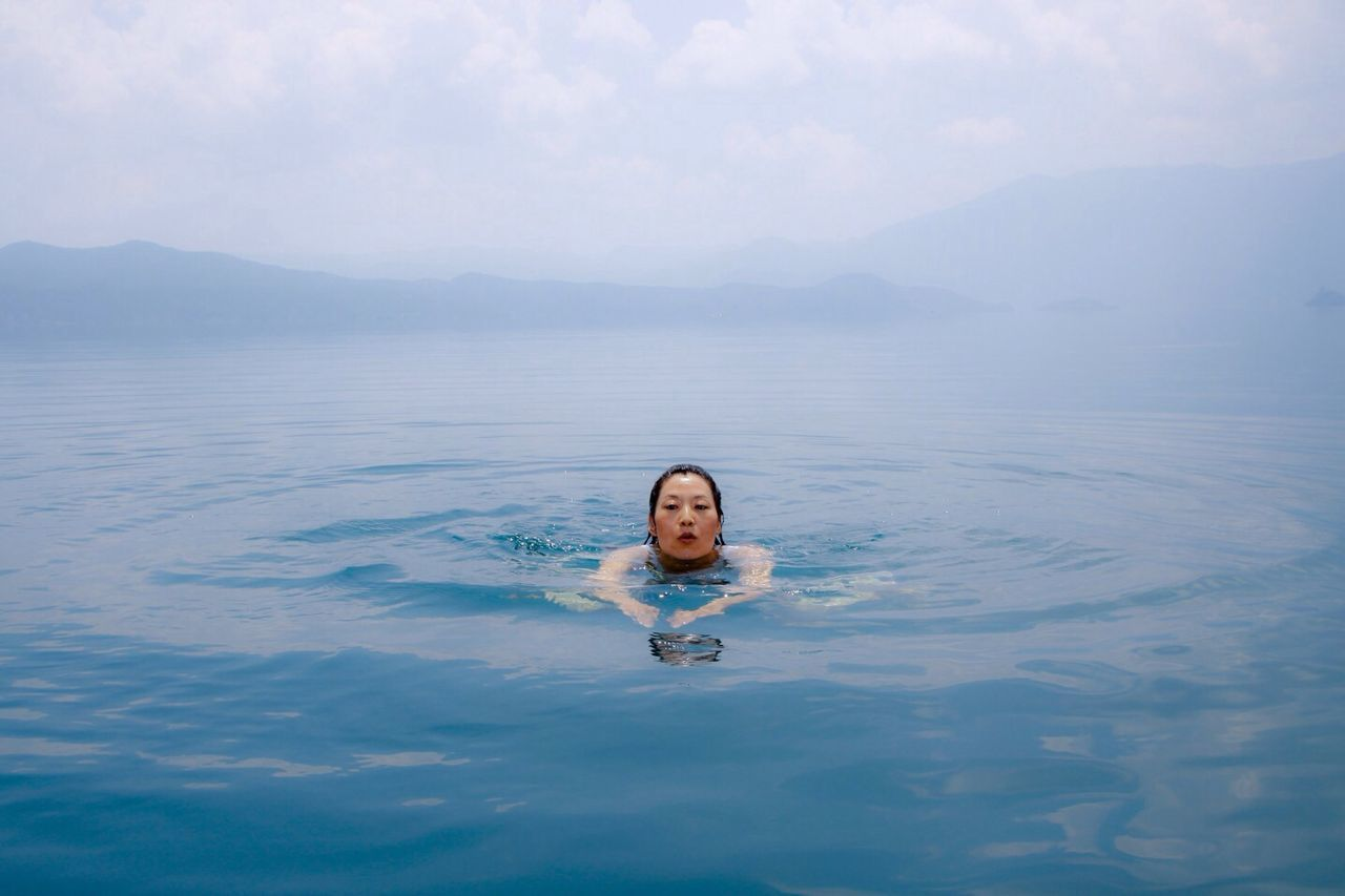 PORTRAIT OF WOMAN SWIMMING IN WATER
