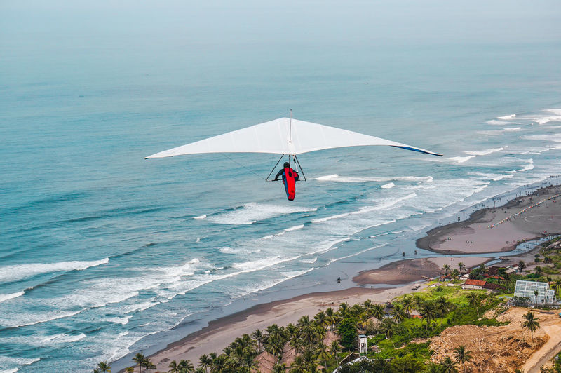 Person Paragliding Over Sea