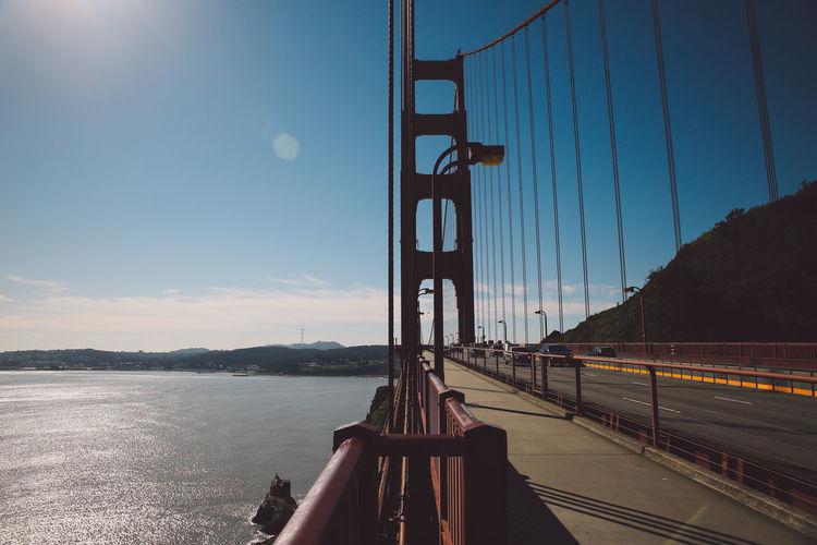 View of suspension bridge over river against sky