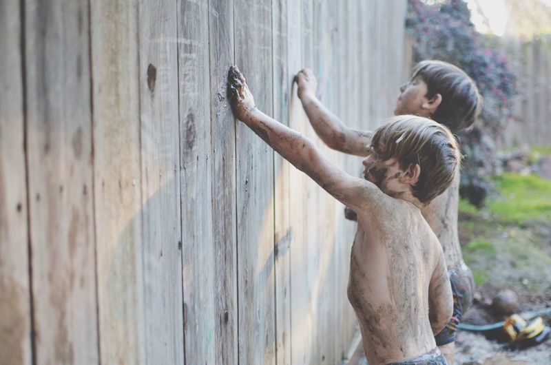 Dirty shirtless boys touching wooden wall