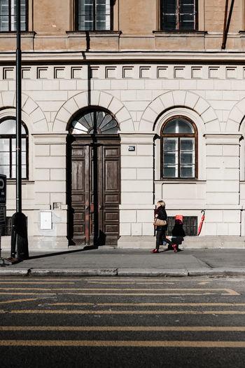 Man walking on footpath against building