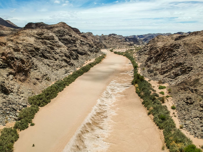 Stunning wide angle aerial drone view of the dry riverbed and mountains near Ai-Ais Hot Springs at the southern end of Fish River Canyon Karas Region of southern Namibia, Africa. Desert Drought Hot Springs Namibia Nature No Water Riverbed Travel Aerial View Ais-ais Arid Climate Beauty In Nature Climate Change Dji Drone View Environmental Conservation Fish River Fish River Canyon Mountain Namibia Desert Nature_collection Oasis Sand Scenics Tourism