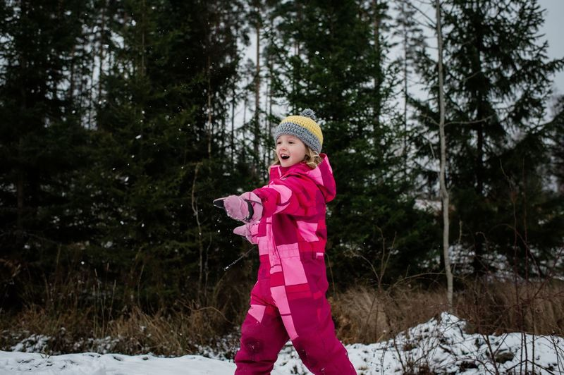 Full length of cute girl standing on snow covered trees
