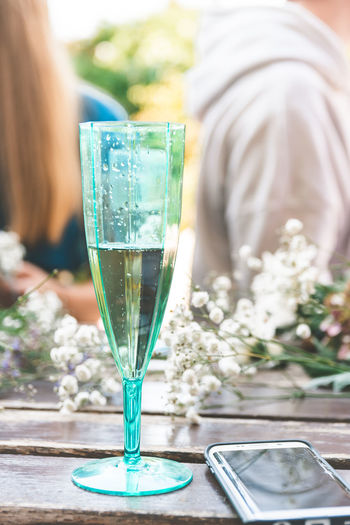 Drink Refreshment Food And Drink One Person Focus On Foreground Glass Alcohol Table Midsection Wine Day Nature Glass - Material Women Real People Close-up Adult Lifestyles Outdoors Flower Arrangement