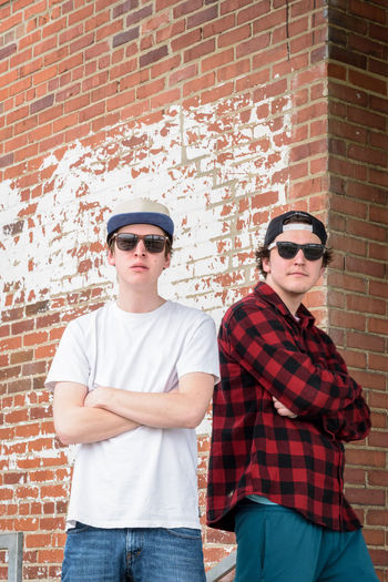 Portrait of young friends standing against brick wall