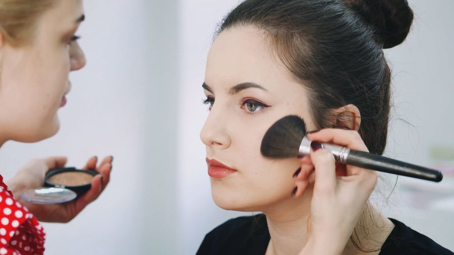 Beautician doing make-up of young woman
