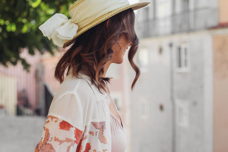 Midsection of woman wearing hat standing outdoors