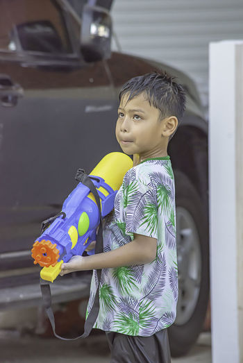 Side view of boy playing with squirt gun