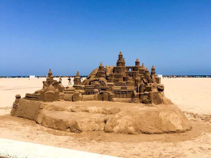 Sand castle at beach against clear blue sky during sunny day