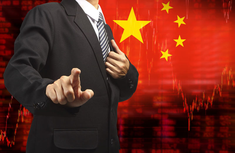 Digital composite image of businessman gesturing while standing against chinese flag