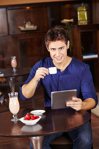 Young man using smart phone in restaurant