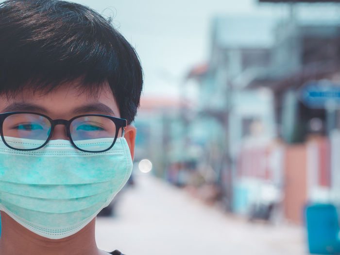 Close-up portrait of boy wearing pollution mask in city