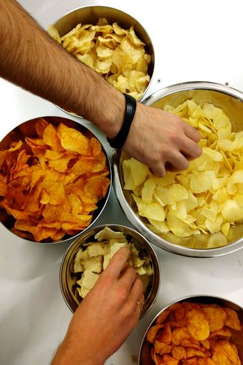Cropped Hands Of People Picking Chips From Container On Table