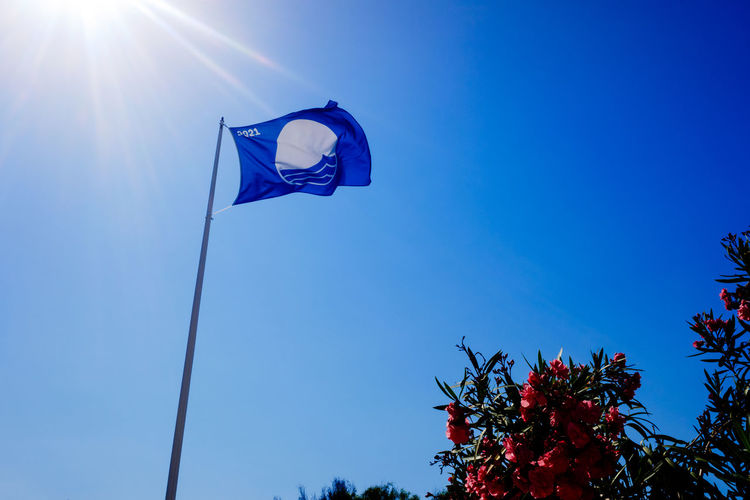 Low angle view of flag against blue sky on sunny day