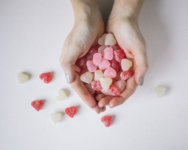 Woman's hand holding candied hearts Human Hand Hand White Background Hand, Candy, Valentines Day, Love, Sweet, Candies, One Person Indoors  High Angle View Temptation Human Body Part Sweet Food Body Part Food Food And Drink Finger