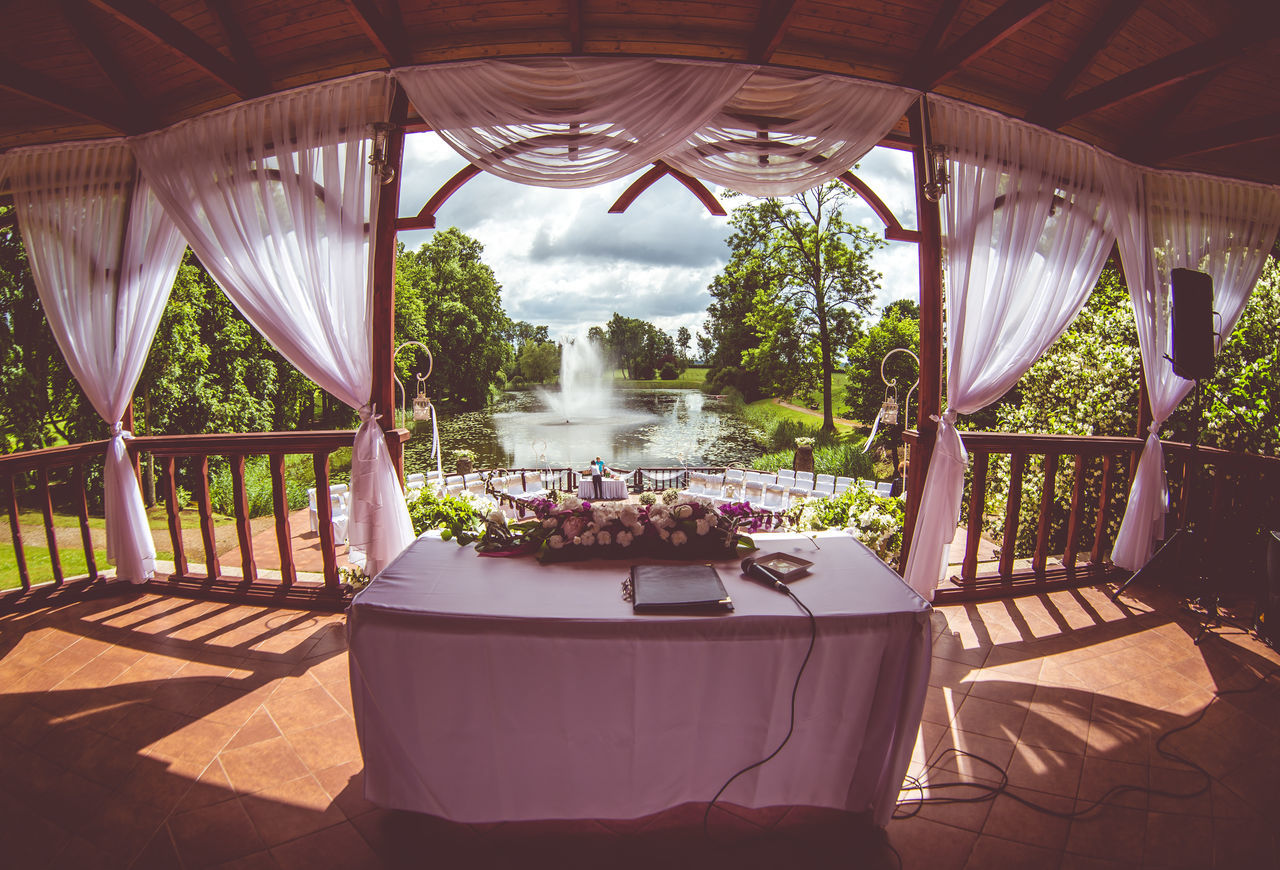 table, potted plant, chair, day, gazebo, no people, luxury, tourist resort, nature, plant, outdoors, curtain, flower, place setting, beauty in nature, luxury hotel, swimming pool, architecture, water, tree