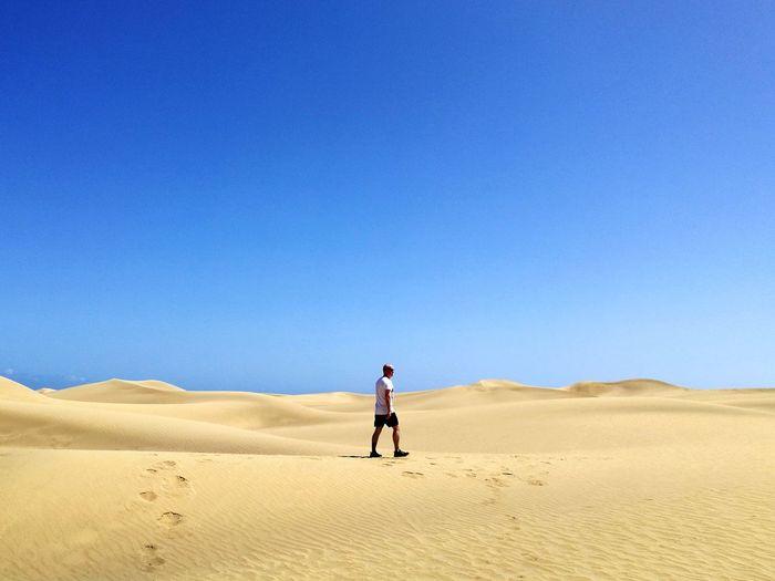 Man walking on desert against clear blue sky
