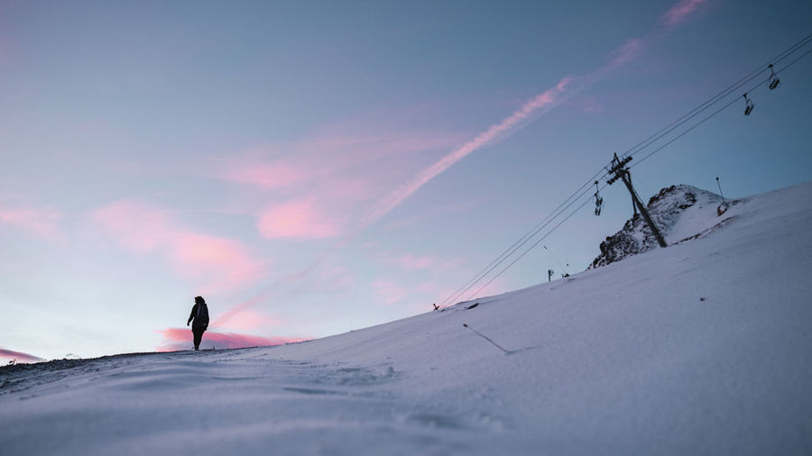 Low angle view of woman walking on snowcapped mountain against sky