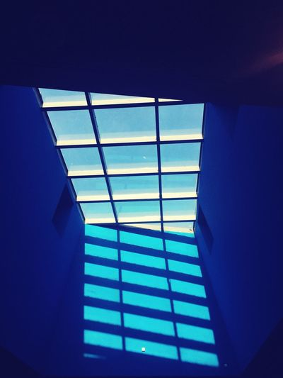 Blue over blue EyeEm Selects Indoors  Low Angle View No People Architecture Blue Pattern Built Structure Window Wall - Building Feature Sunlight Sky Geometric Shape Nature Design Building Day Glass - Material Ceiling Glass Directly Below