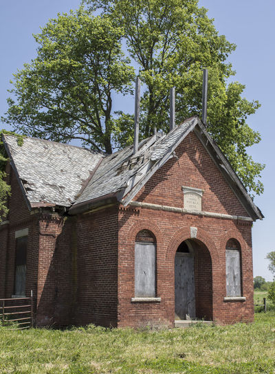 Exterior Of Old School Building On Grassy Field