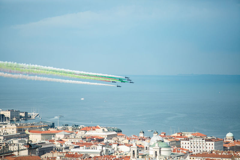 Trieste, Italy - October, 4 2017: Airshow Training of PAN Frecce Tricolori -Tricolour Arrows. Flight patrol during aircraft performance.The team flies the Aermacchi MB-339-A/PAN TriesteSocial Aerobatics Architecture Beauty In Nature Blue Building Exterior Built Structure Cityscape Clear Sky FreccieTricolori High Angle View Horizon Over Water Jet Nature Nautical Vessel Outdoors Pan Scenics Sea Vapor Trail Water