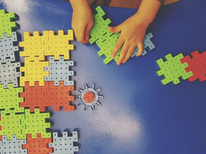Close-Up Of Person Playing Puzzle At Table