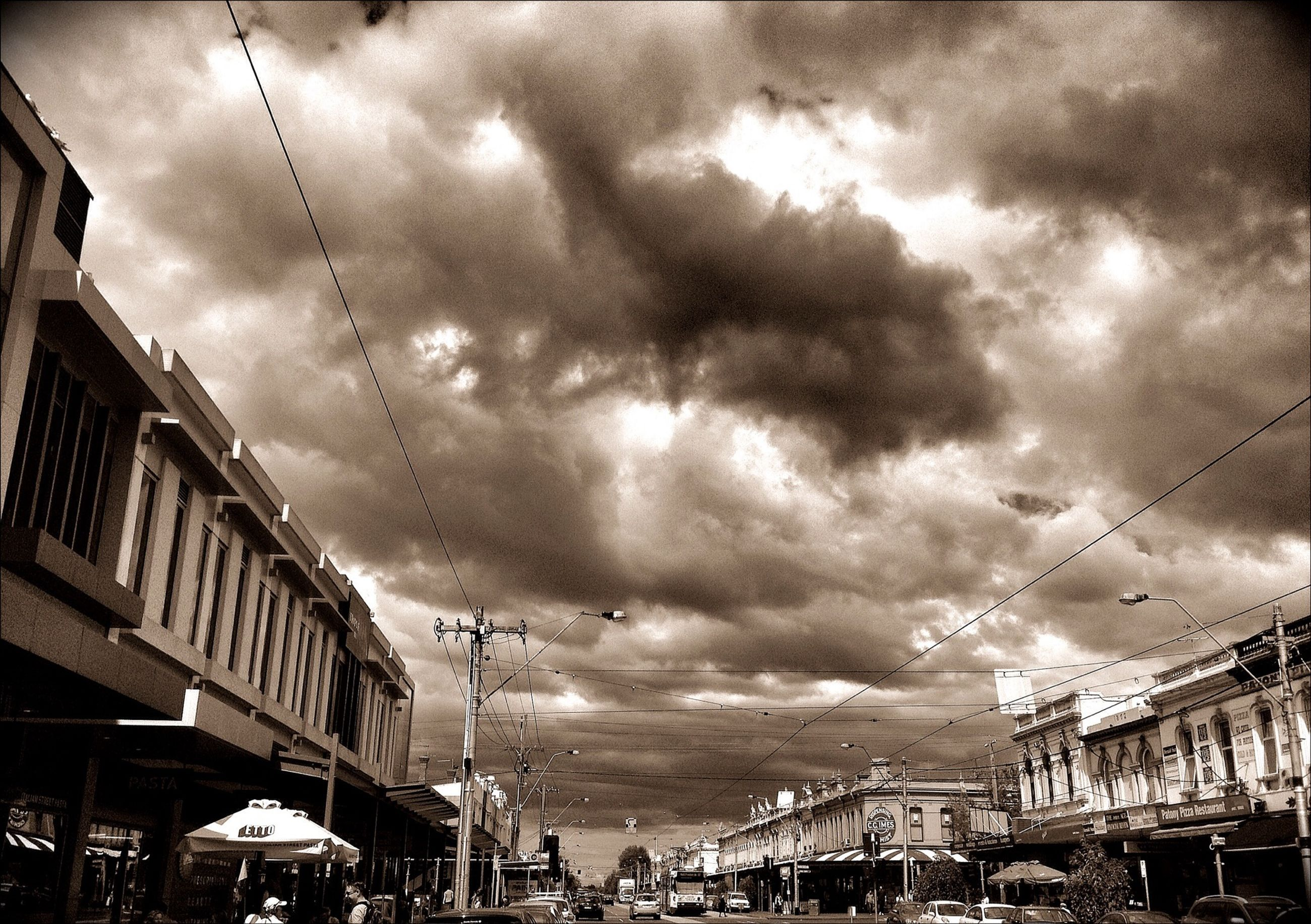 sky, cloud - sky, cloudy, building exterior, architecture, built structure, weather, storm cloud, overcast, low angle view, cloud, city, transportation, dusk, power line, residential building, residential structure, outdoors, mode of transport, dramatic sky